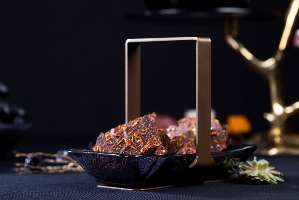 Ale is a charming twin nuts and snacks bowl with a metal loop handle. It is tainted in deep night blue and adorned with the playful Perky Chrysanthemum pattern. Ale is presenting dark chocolate with bright orange sprinkles and is positioned in a dark Halloween elegant table setting.