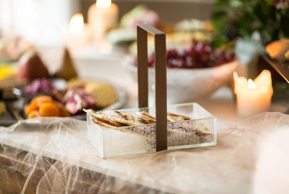 Candy is a lovely turtledove cream coloured bread basket in our delicate Lace pattern with a comfortable handle. Candy is filled with bread pieces on top of a table specially set up for CHeese and frits themed buffet.