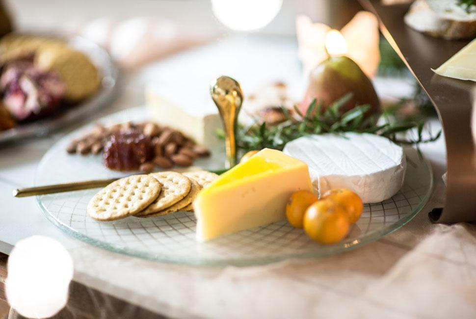 Diana is a round cheese platter with handle in cute pearly white colour, adorned with our royal Filigree pattern. Diana is presenting combination of cheese, fruits and and crackers
