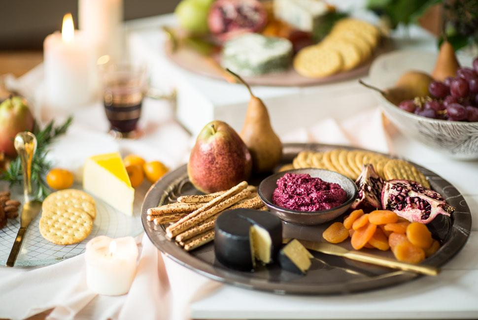 Elyn is a round serving dip platter teamed with a small bowl, both in dark doe brown with our vivid Vivace pattern. Elyn is on a full beautiful table and is presenting cheese, fruits and crackers