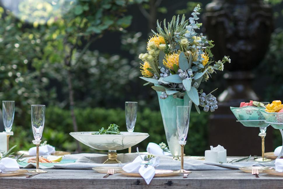 Table Setting Paris is a flower vase on bronze base. Paris is used as a centrepiece in a table setting for Australia day with native Australian flowers in yellow and green