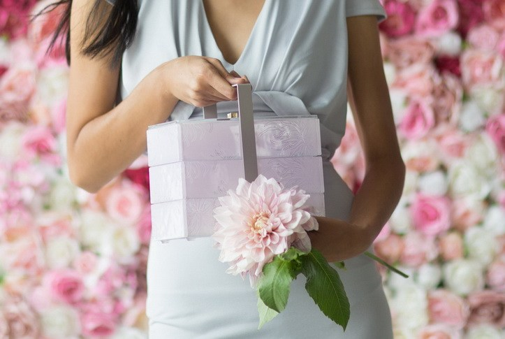 A woman's hands holding a pink bento box and a flower