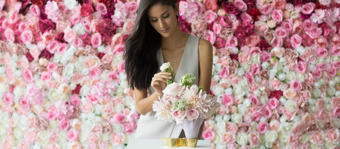 A woman arranging a bouquet in a beautiful pink vase