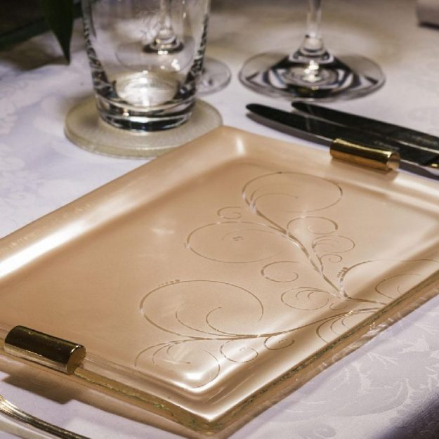 Cameo Rose Gold Charger Plate, Nora Set/2 Floral Charger Plates with Shiny Brass Handles on table.