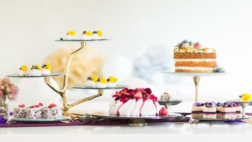 Designer glass cake stands, plates and tall pedestal cake stand by Anna Vasily with lamingtons and a Pavlova.