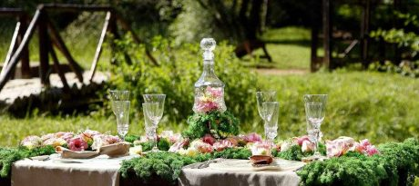A fary like table setting in a very green environment outdoors. Flowers, forest feeling with glass plates and glasses.