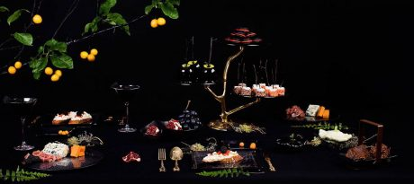 Finger food platters for Halloween. Dark and mysterious Halloween themed table setting consisting of deep night blue 3 tiered high tea stand on bronze tree, snack basket with chocolate, square plates with floral pattern with appetizers, fruit bowl with fruits inside and finger food platter in Filigree pattern. The composition is closed with a real tree branch on top.