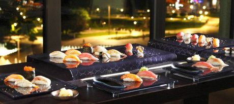 Beautiful sushi tableware in dark blue with night cityscape on the background.