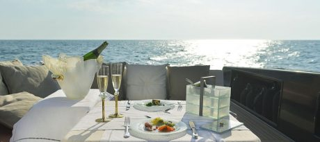 Blue Dinner Set Romantic wedding anniversary escape with luxury dinnerware champagne bucket, 2 champagne glasses, light blue dinner plates and designer bento box with background the sea