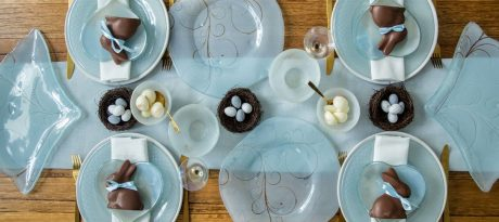 A beautiful blue tablescape covered in blue plates chocolate eggs, and other Easter decorations.